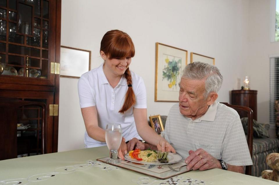 A caregiver serves a senior at home.